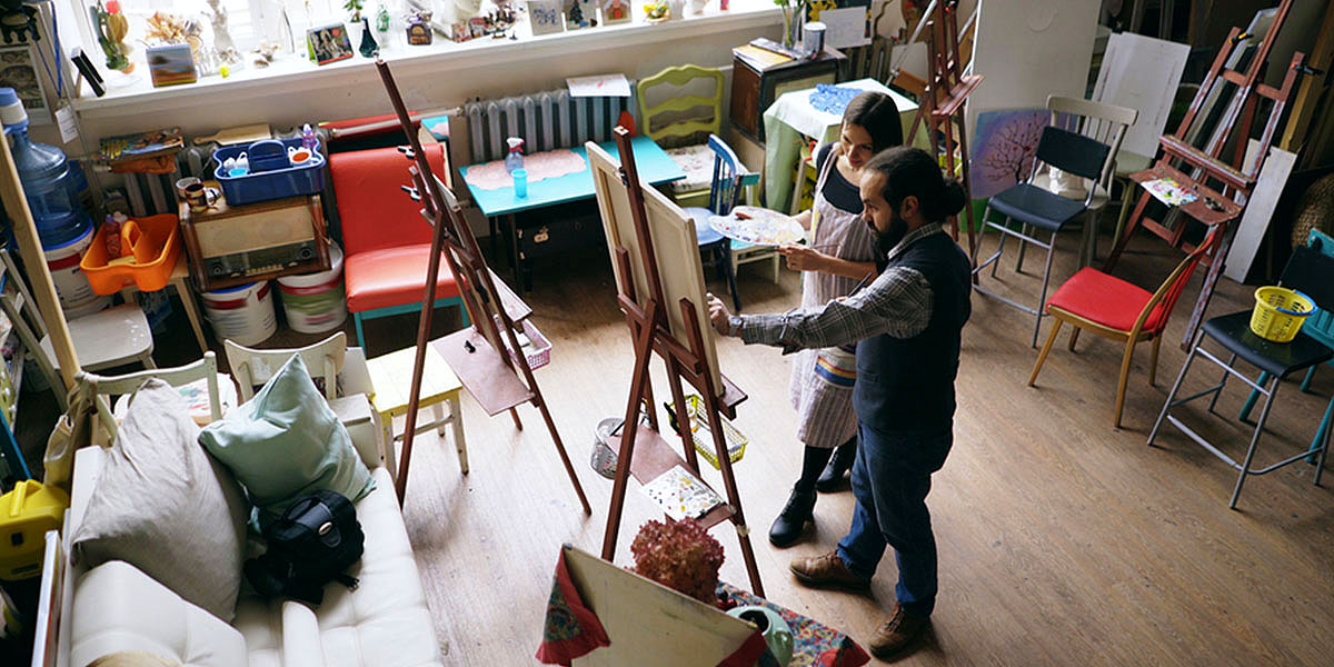 ACCOB member in art studio with teacher oil painting