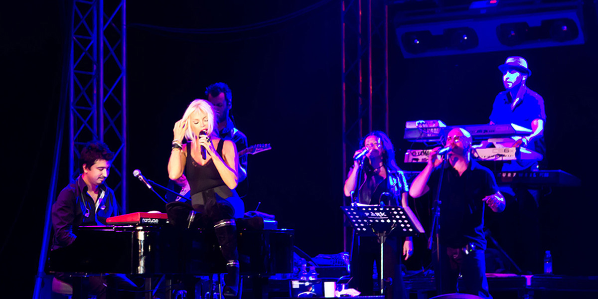 Singer performing live on stage with musicians and backing vocalists