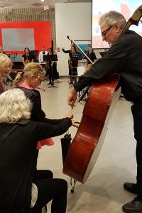 Double bass player shows his instrument to a child in the Art Gallery of Burlington